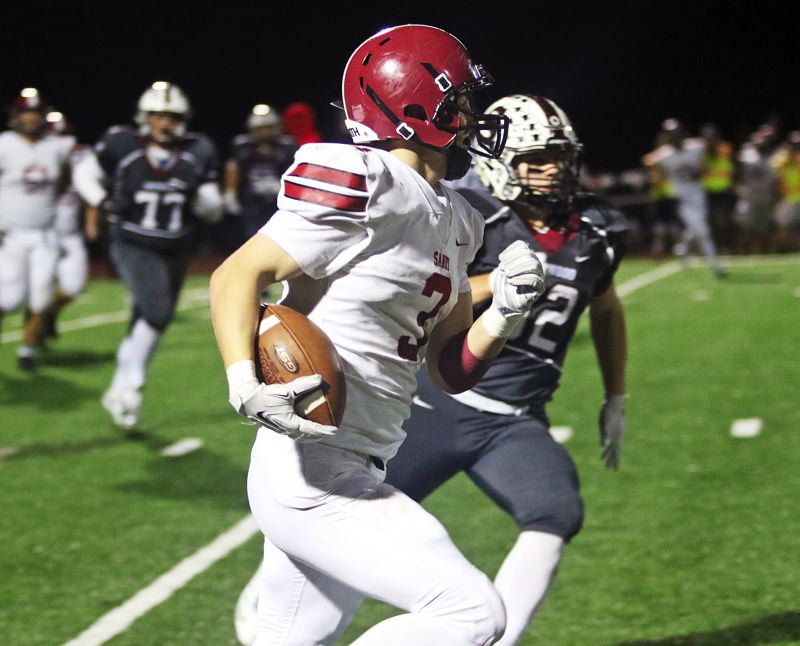 TIMES PHOTO: DAN BROOD - Sandy junior Colby Carson heads up field after catching a pass during Friday's game at Sherwood.