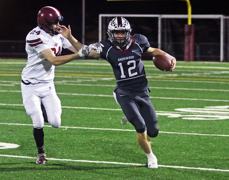 TIMES PHOTO: DAN BROOD - Sherwood senior quarterback Seth Bernhardt (12) tries to get away from Sandy junior Zach Miller during Friday's state playoff game.