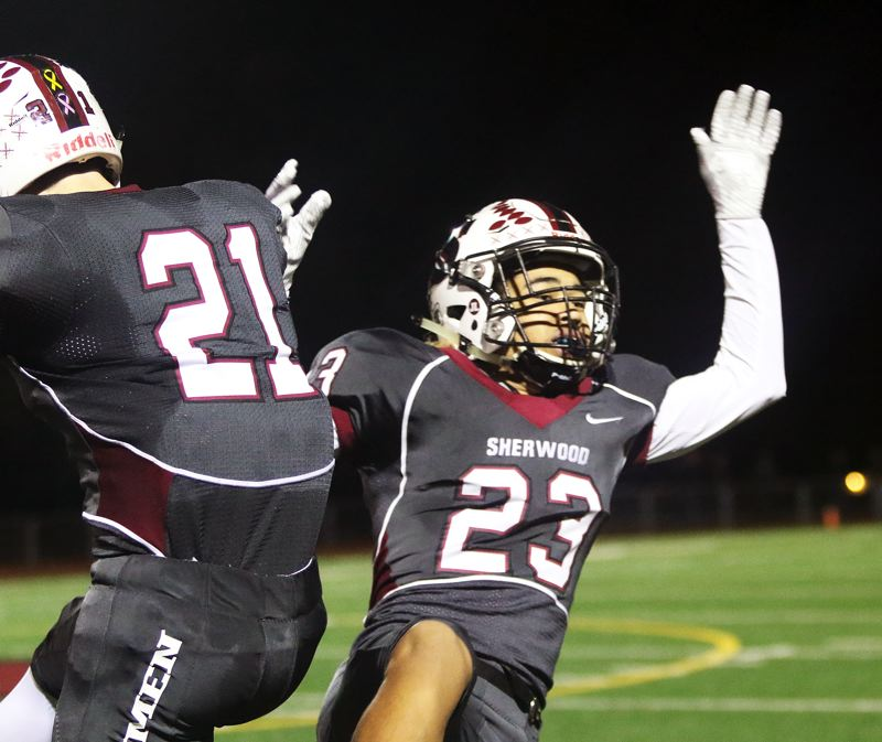 TIMES PHOTO: DAN BROOD - Sherwood junior Jamison Guerra (right) celebrates with senior Kaden Rhinehart following his 51-yard touchdown run.