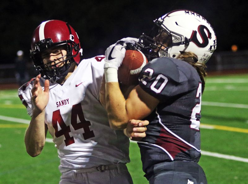 TIMES PHOTO: DAN BROOD - Sandy senior Dallin Thomas (left) and Sherwood sophomore Jack Causey battle for the ball during Friday's state playoff game.