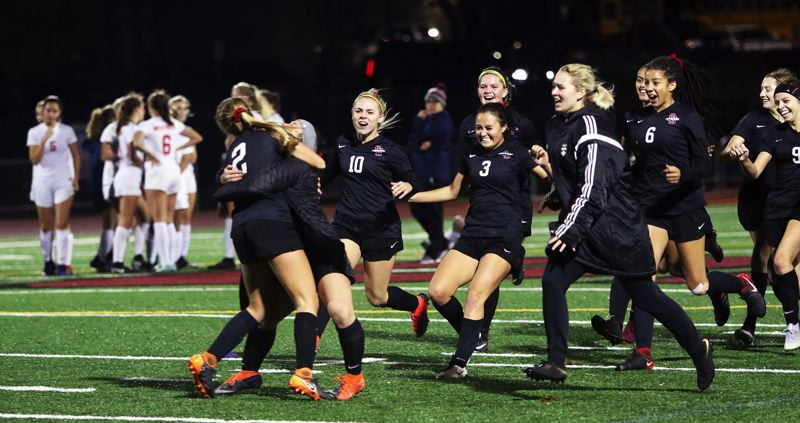TIMES PHOTO: DAN BROOD - Members of the Sherwood High School girls soccer team celebrate following the winning goal by sophomore Morgen Fried (2) during the penalty kick shootout with Westview.