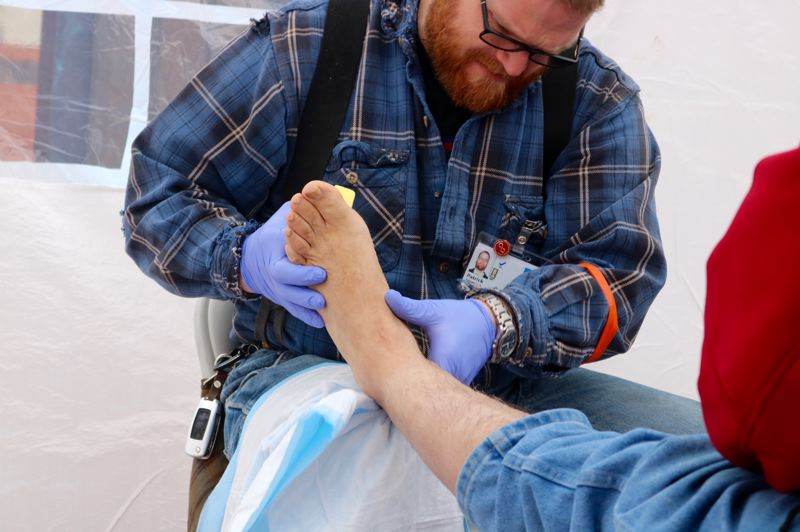 TRIBUNE PHOTO: ZANE SPARLING - Free foot care is provided to a person at the student-run Health Care Equity Fare on Saturday, Nov. 3 in downtown Portland.