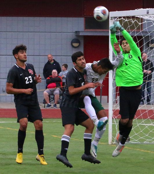 PAMPLIN MEDIA GROUP: BRIAN MONIHAN - David Douglas goalie Andy Borbon punches a ball away before West Linn striker Phillip Jonsson can connect for a header in the late stages of the Scots' win Saturday.