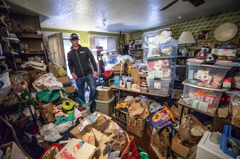 TRIBUNE PHOTO: JONATHAN HOUSE - Chris Gage, president and Owner of Steri-Clean Oregon, steps around large piles of goods in a hoarder home.