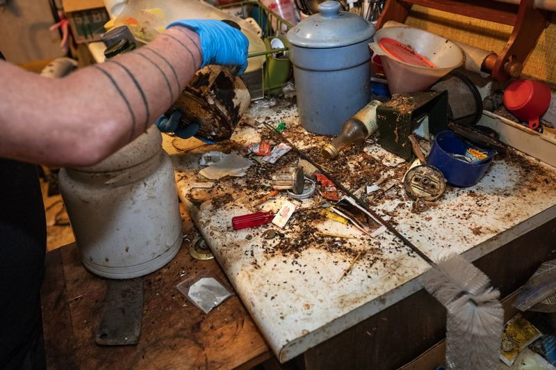 TRIBUNE PHOTO: JONATHAN HOUSE - PIles of unused items and mouse feces pile on the kitchen counter of a hoarder home in SE Portland.