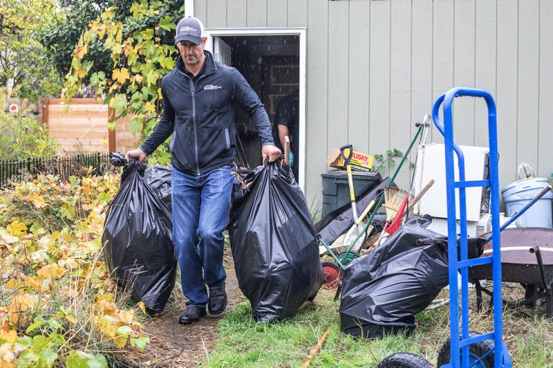 TRIBUNE PHOTO: JONATHAN HOUSE - Chris Gage, president and Owner of Steri-Clean Oregon, helps remove trash from a hoarder home.