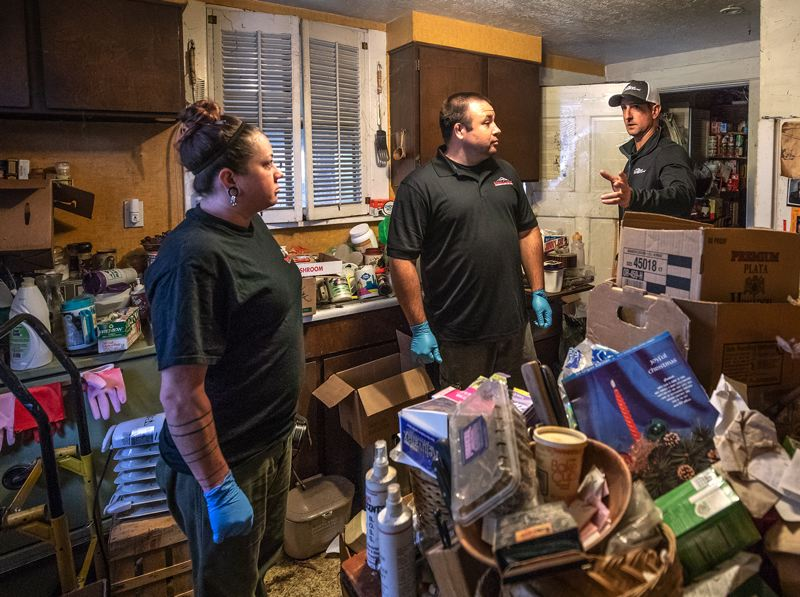 TRIBUNE PHOTO: JONATHAN HOUSE - Chris Gage, president and Owner of Steri-Clean Oregon, right, chats with techs David Brown and Sarah DeHart about how to best clean a hoarder home in SE Portland.