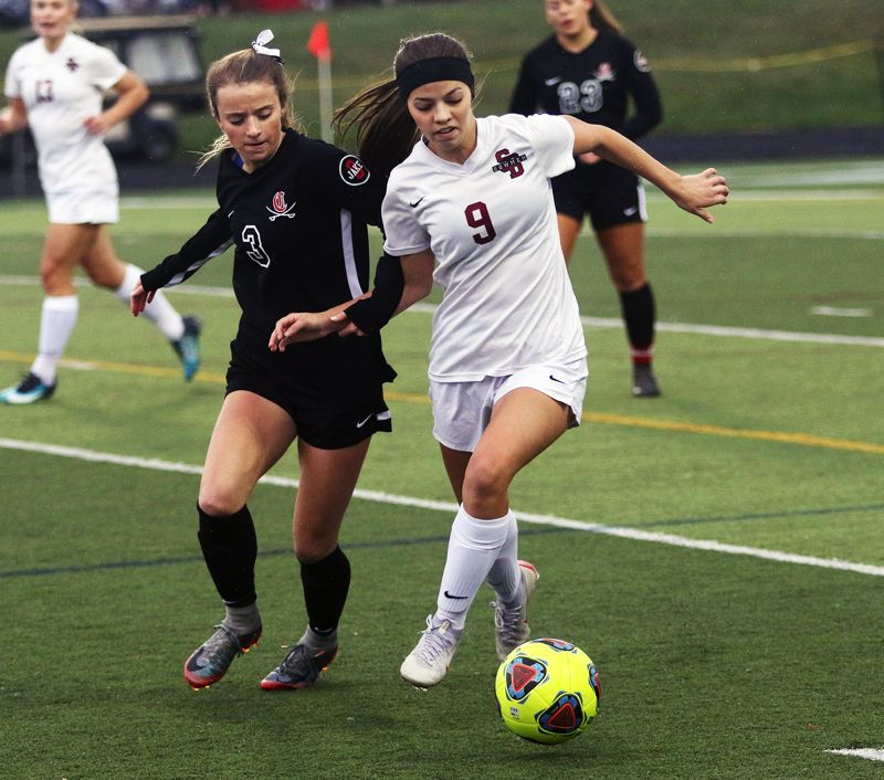 TIMES PHOTO: DAN BROOD - Sherwood junior Jillian Leroux (9) stays ahead of Clackamas senior Peyton Fendrich in a race for the ball during Saturday's state playoff quarterfinal match.