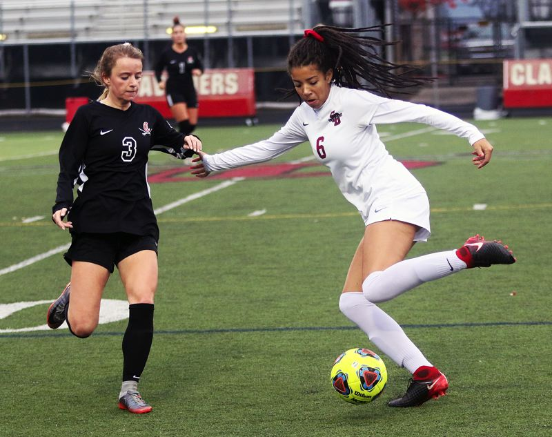 TIMES PHOTO: DAN BROOD - Sherwood sophomore Kylah Williams (right) looks to boot the ball past Clackamas senior Peyton Fendrich during Saturday's state playoff match.