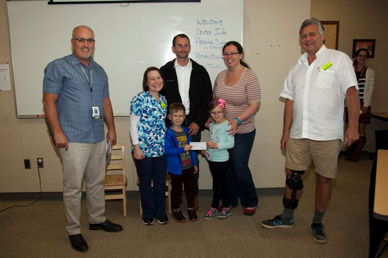 Rotary President Steve Leitz, right, presents a $1,000 check to the Gladstone Center for Children & Families for kindergarten literacy. Also pictured from left are GCCF Director Jere Applebee; Thassa, Logan, Chris Cole, and Marian and Megan Wohlwend.