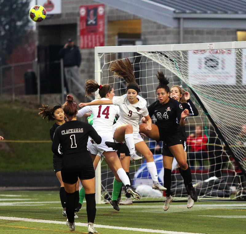 TIMES PHOTO: DAN BROOD - Sherwood seniors Alex Verkamp (14) and Jillian Leroux go up for the ball during the second half of Saturday's state playoff match at Clackamas.