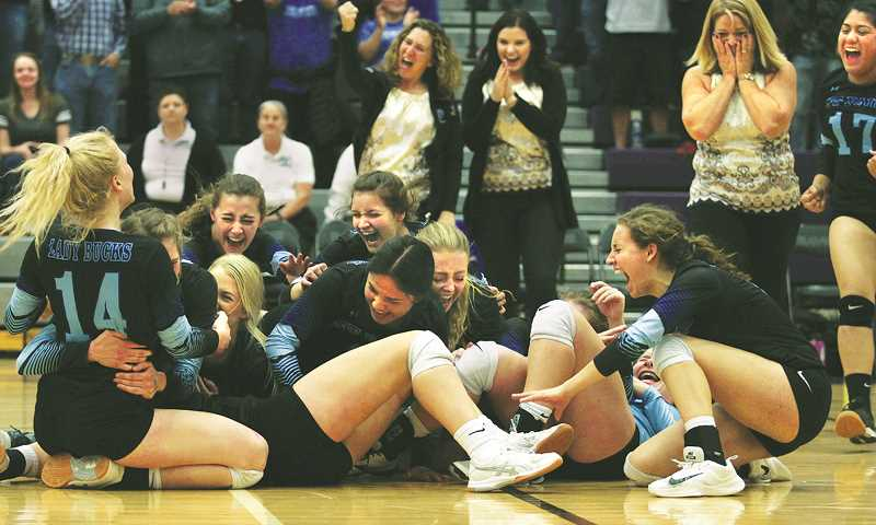 PHIL HAWKINS -- WOODBURN INDEPENDENT - The St. Paul volleyball team collapses in the center of the court in celebration after scoring the match-winning point against the Powder Valley Badgers, delivering the first state volleyball title in program history.