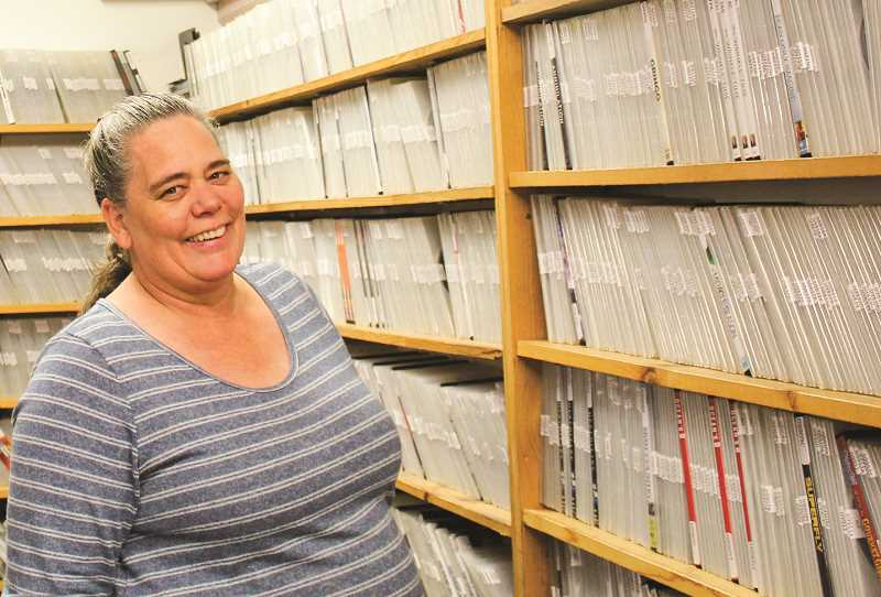 JASON CHANEY/ CENTRAL OREGONIAN  - Video Hut owner Kim Atkinson poses for a photo near the entrance of her video storage area.
