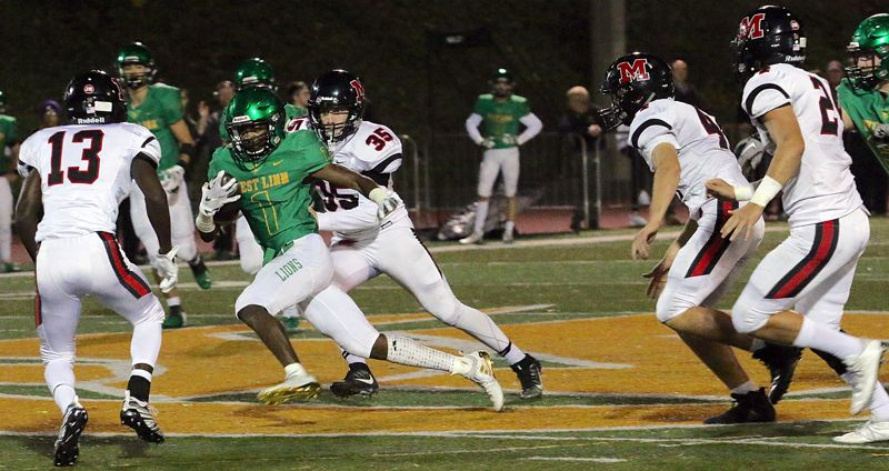 TIDINGS PHOTO: BRIAN MONIHAN - West Linn senior running back Dawson Jolley cuts through the McMinnville defense on his way to 250 rushing yards and three scores in the Lions' 70-35 win in the first round of the Class 6A state playoffs on Friday at West Linn High School.