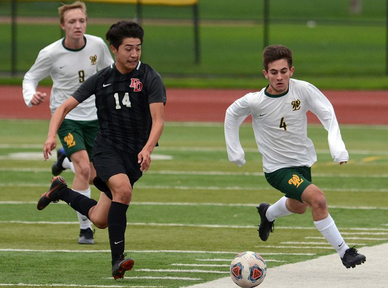 PAMPLIN MEDIA GROUP PHOTO: DAVID BALL - West Linn senior Michael Phillips (right) races David Douglas' Rigo Mendez to the ball during the Lions' 2-0 loss at David Douglas in Saturday's Class 6A state quarterfinal.