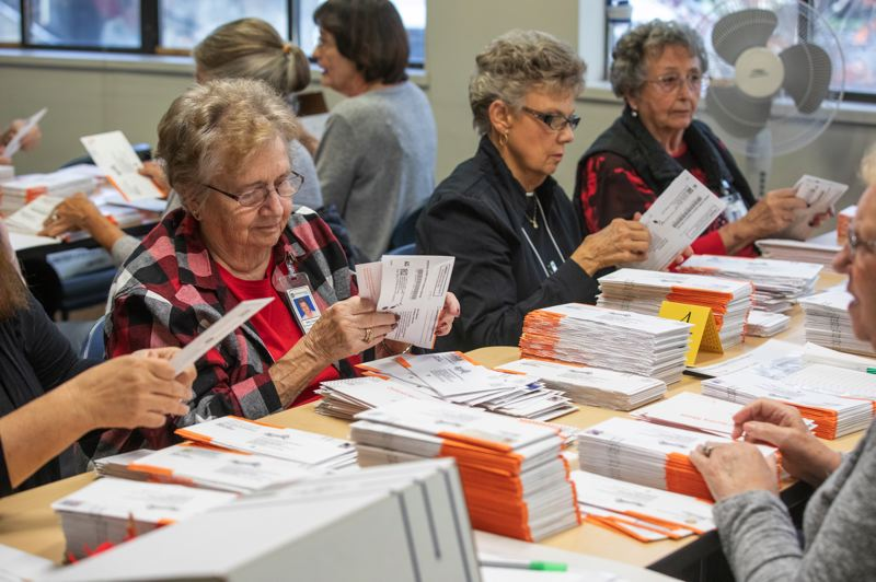 TIMES PHOTO: JONATHAN HOUSE - Volunteers count ballots ahead of Tuesday's election deadline. Oregon's vote-by-mail system means a portion of the results will be known shortly after 8 p.m. Tuesday.