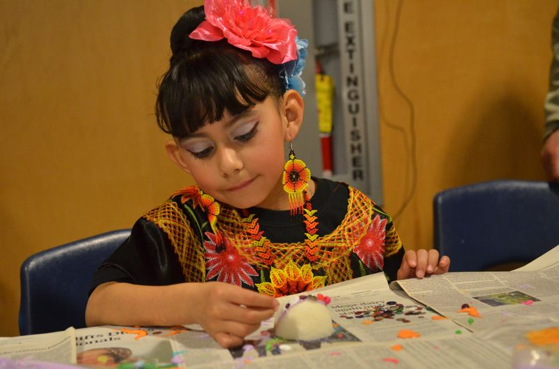 SPOKESMAN PHOTO: VERN UYETAKE  - Alondra Barajas works on a Day of the Dead craft.