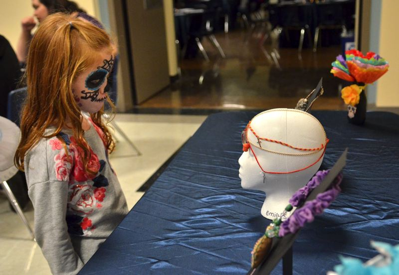 SPOKESMAN PHOTO: VERN UYETAKE  - Anna Marks checks out the are display of Day of the Dead inspired student work.
