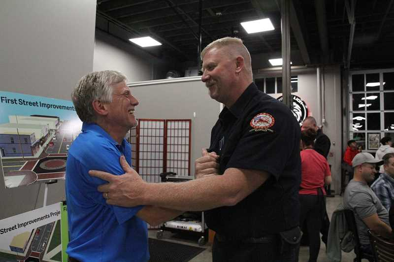LINDSAY KEEFER - Eric Swenson (left), mayor-elect of Woodbur, shakes hands with Lt. Robb Gramzow of Woodburn Fire District, which saw its operating levy approved by voters. Swenson and the fire district held watch parties at Metropolis Marketplace, with dozens of supporters showing up to see the earliest results coming in Tuesday night.
