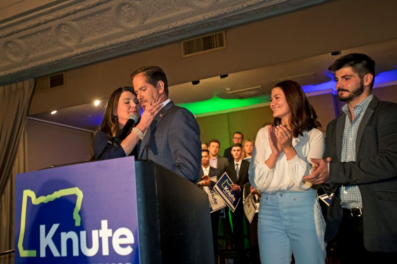 TIMES PHOTO: JAIME VALDEZ - State Rep. Knute Buehler, at lectern, is comforted Tuesday as early returns showed Gov. Kate Brown retaining her seat.