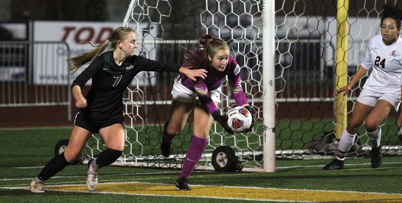 TIDINGS PHOTO: MILES VANCE - West Linn junior Rosie Larsen (left) challenges Clackamas senior goalkeeper Hallie Byzewski during the Lions' 1-0 loss to the Cavaliers in the Class 6A state semifinals at West Linn High School on Tuesday.