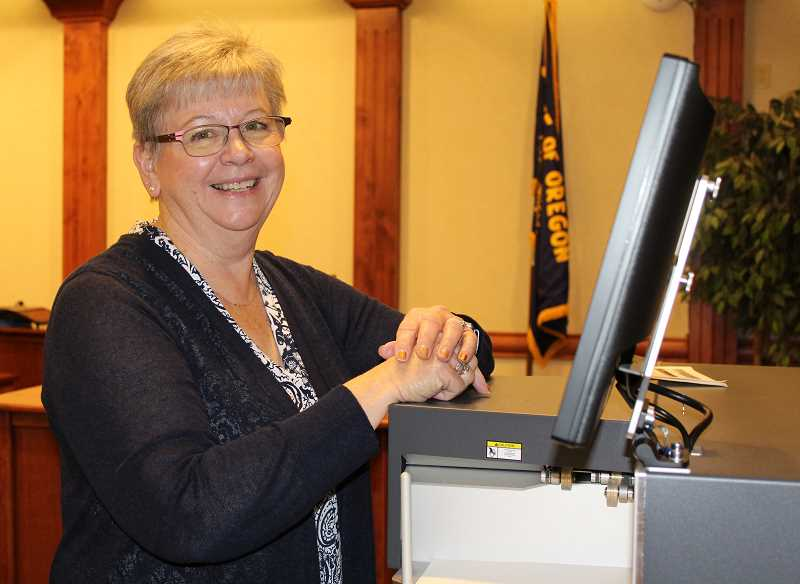 HOLLY M. GILL/MADRAS PIONEER - Retiring Jefferson County Clerk Kathy Marston checks the ballot counting machine prior to the election. The Nov. 6 election will be Marston's last as clerk.