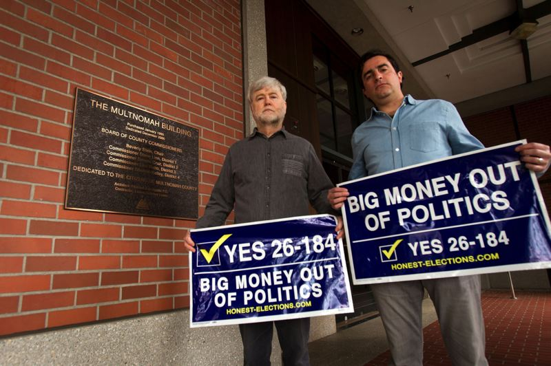 TRIBUNE FILE PHOTO - City contributon limits advocates Dan Meek (left) and Jason Kafoury, shown with signs from their successful 2016 Multnomah County campaign measure. Fresh from overwhelming victory at the Portland batllot, they now plan a 2020 statewide measure.