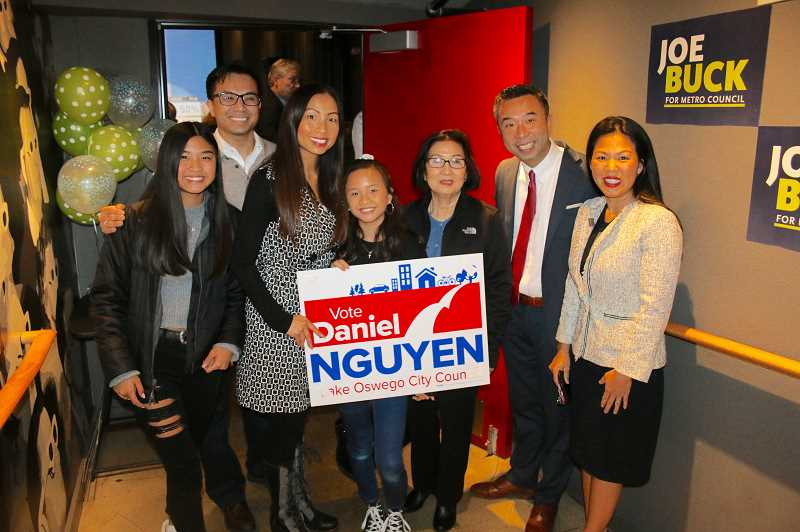 REVIEW PHOTO: J. BRIAN MONIHAN - Daniel Nguyen and his wife Katherine pause with Nguyen's mother and extended family during Tuesday night's gathering at the Lake Theater and Café to celebrate his election to the Lake Oswego City Council.