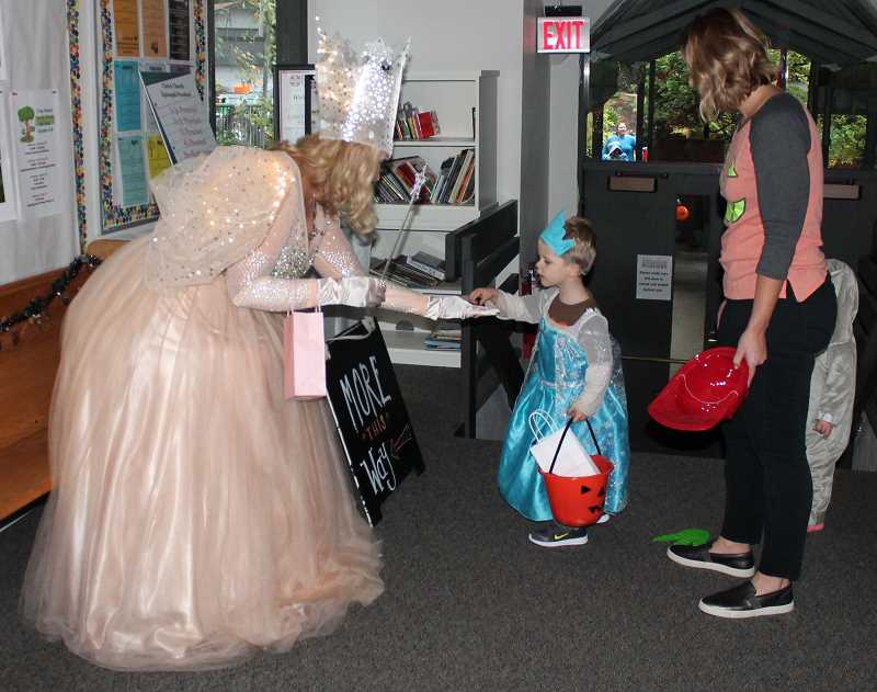 REVIEW PHOTO: CLAIRE HOLLEY - Glenda the Good Witch (aka Recreation Superintendent Jan Wirtz) hands out treats to Drew and Margo Batchelder at last week's Monster Mash event.