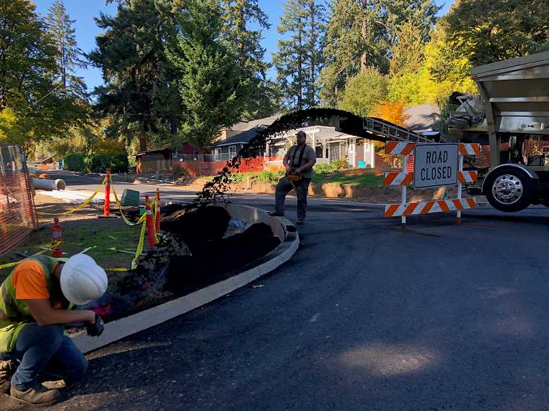 PHOTO COURTESY OF CITY OF LAKE OSWEGO  - Construction crews fill stormwater swales with soil ahead of the arrival of plants that will help the catchment system filter and treat stormwater before it reaches Tryon Creek.