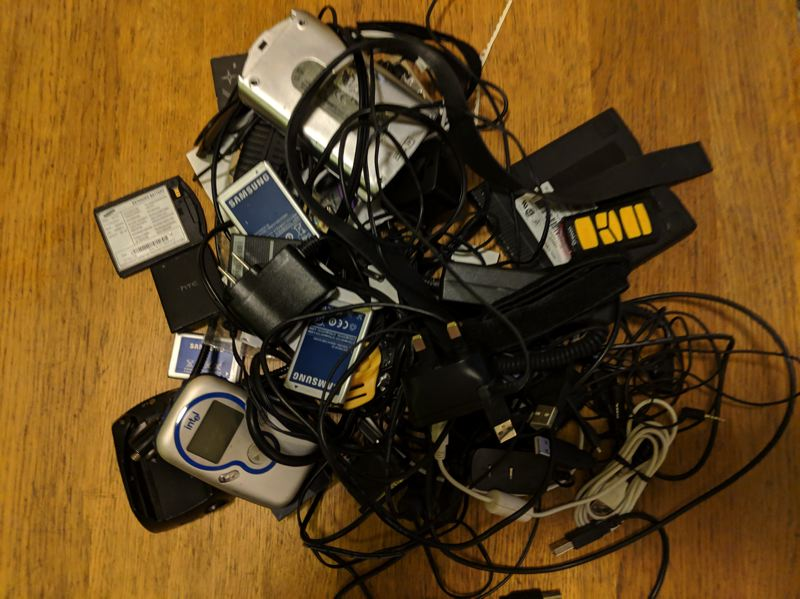 PAMPLIN MEDIA GROUP: JOSEPH GALLIVAN  - A Gordian knot of old cables and connectors. Note the silver and blue Intel MP3 player on the left, from when the chip maker dabbled in consumer devices. Its all headed to Free Geek.
