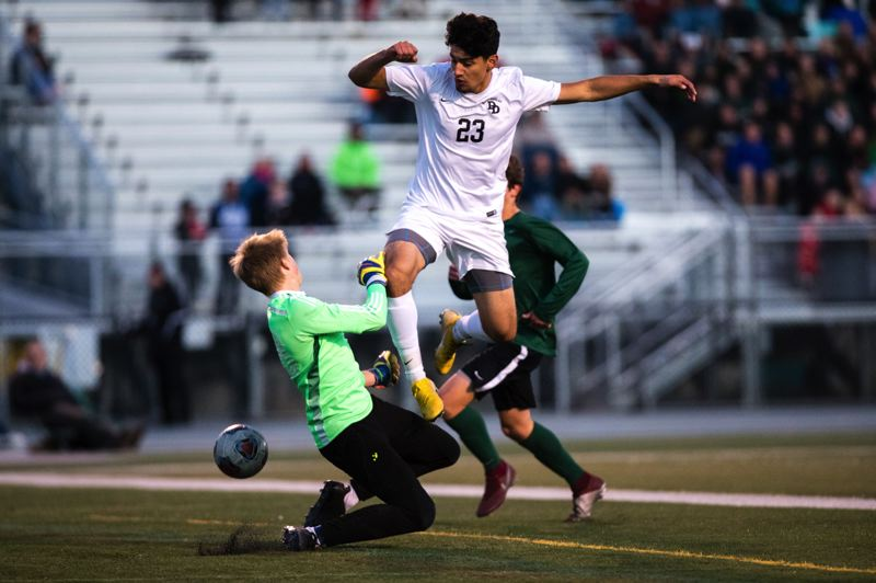 FOR THE OUTLOOK: ROB KERR - David Douglas striker Angel Vidas goes into the air to avoid Summit goalie Khael Engelman during the Storms 2-1 overtime win in Tuesdays state semifinal match.
