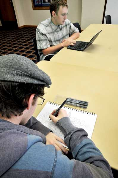 GARY ALLEN - Newberg High School junior Nathan Beals (foreground) pens a drawing of a team he went to Africa with on a missionary trip, while senior Donovan Lewis uses software to draw a backpack that converts to a chair. It is part of his senior project at the school.