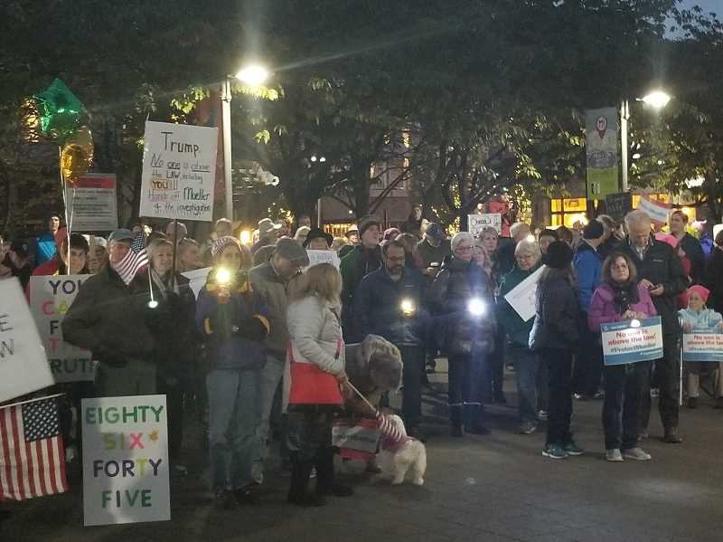 REVIEW PHOTO: GARY M. STEIN - More than 150 people gathered Thursday night in Lake Oswego's Millennium Plaza Park, where they turned on flashlights to 'shine a light on the dark corners of the Trump administration.'
