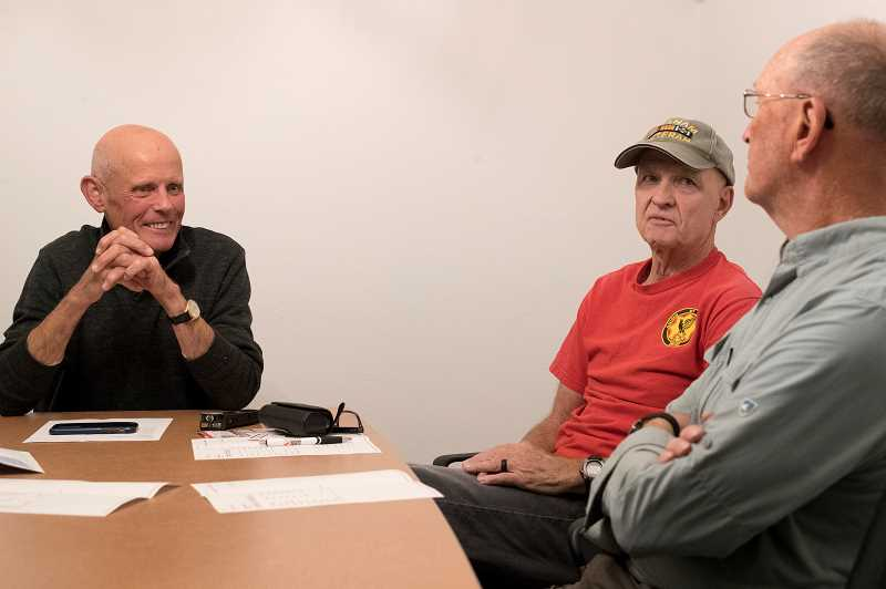 TIMES PHOTO: JAIME VALDEZ - Tigard High School Vietnam veterans Howard Boyte, left and Gary Chamberlain chat with fellow Vietnam veteran Mike Miles at Symposium Coffee recently. The trio hope to collect memories of fellow veterans, their families and others with the ultimate goal of hosting a future reunion.
