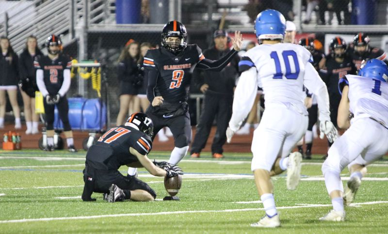 PAMPLIN MEDIA: JIM BESEDA - Gladstone's Jaxon Jedrykowski (17) sets the ball down as Mateo Burgos (9) steps into a 47-yard field goal that lifted the Gladiators to a 30-27 win over La Grande in Friday's 4A quarterfinals.