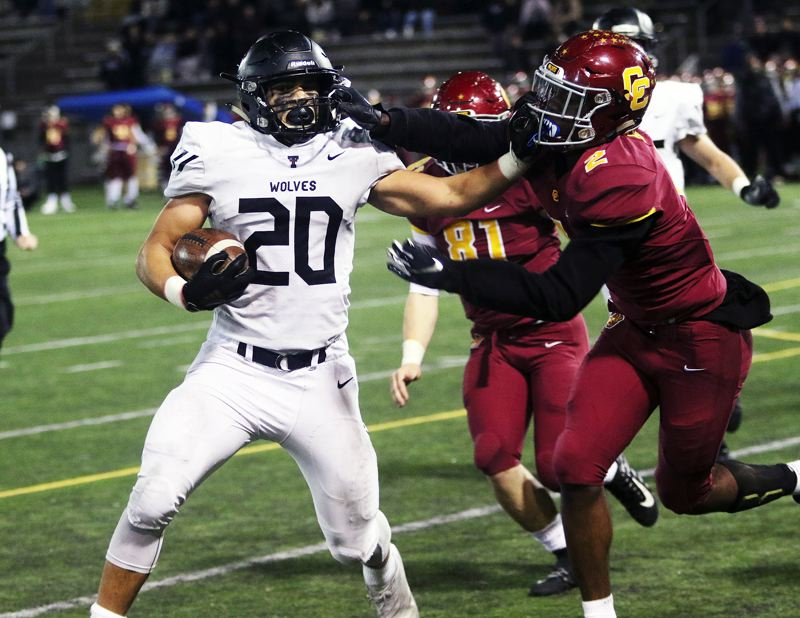 TIMES PHOTO: DAN BROOD - Tualatin junior John Miller (left) tries to power his way past Central Catholic senior Germaine Flentroy during the overtime session in Friday's Class 6A state playoff second-round game.