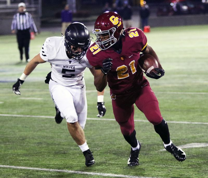 TIMES PHOTO: DAN BROOD - Central Catholic junior Miles Jackson (21) tries to get past Tualatin senior Kyle Kamp during Friday's game.