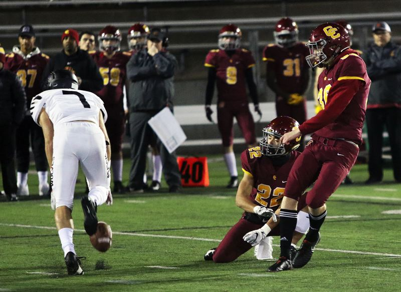 TIMES PHOTO: DAN BROOD - Tualatin junior Luke Marion (left) blocks a field goal attempt by Central Catholic senior Fritz Kabeiseman during Friday's game.