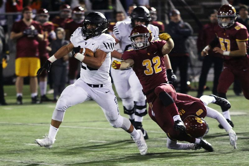 TIMES PHOTO: DAN BROOD - Tualatin junior John Miller (left) breaks into the clear for a 49-yard run during Friday's state playoff game with Central Catholic.