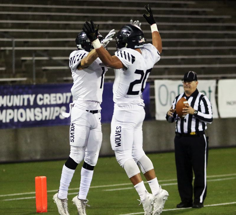 TIMES PHOTO: DAN BROOD - Tualatin senior Jett Searle (left) and junior John Miller celebrate following Searle's 18-yard touchdown catch during Friday's game.
