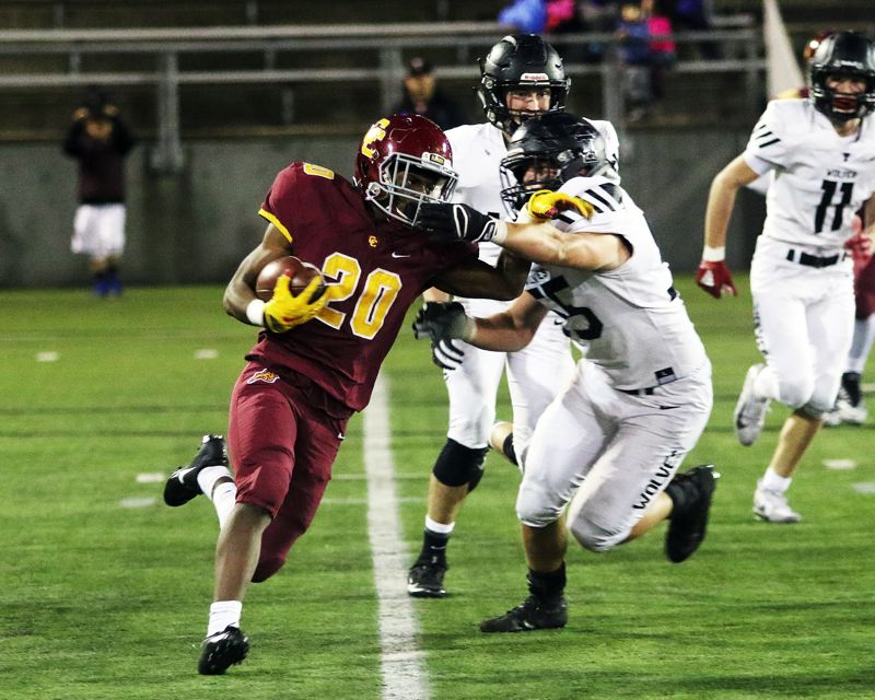 TIMES PHOTO: DAN BROOD - Central Catholic junior Elijah Elliott (20) tried to get past Tualatin junior Cody Van Meter during Friday's Class 6A state playoff game.