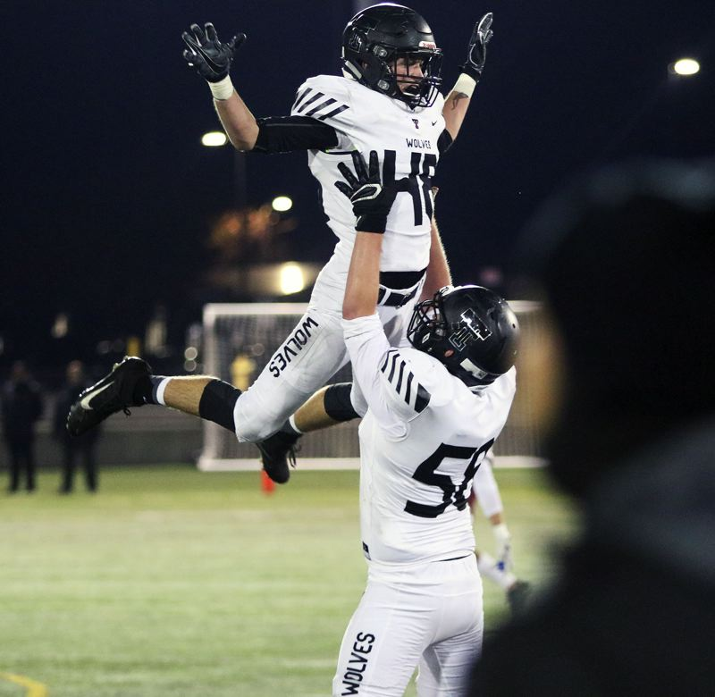 TIMES PHOTO: DAN BROOD - Tualatin senoir Garrett Boespflug (left) and senoir Dane Nolin celebrate following Boespflug's second-quarter interception.