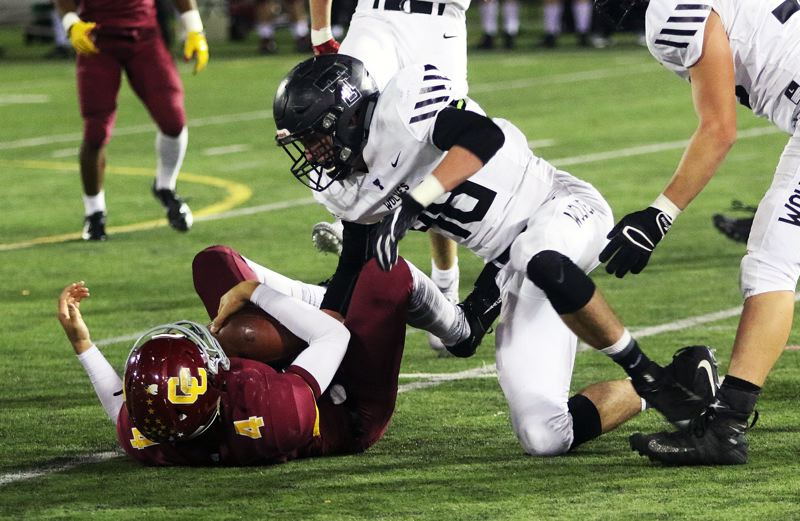 TIMES PHOTO: DAN BROOD - Tualatin senior linebacker Garrett Boespflug (48) sacks Central Catholic quarterback Cade Knighton.