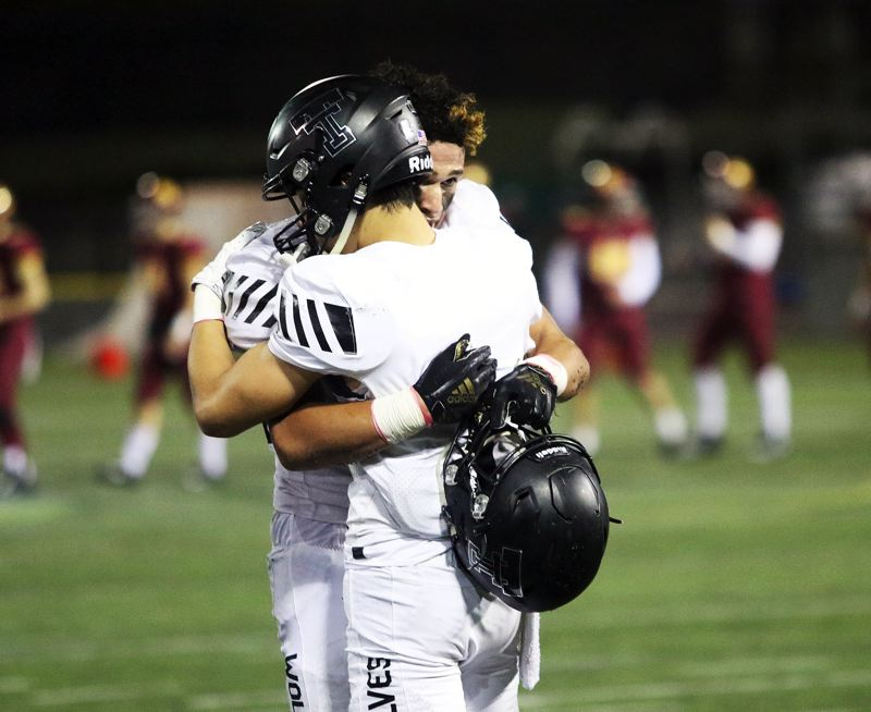 TIMES PHOTO: DAN BROOD - Tualatin junior John Miller (left) and senior Jett Searle console each other following Friday's state playoff game. The Wolves fell 28-21 in overtime against Central Catholic.