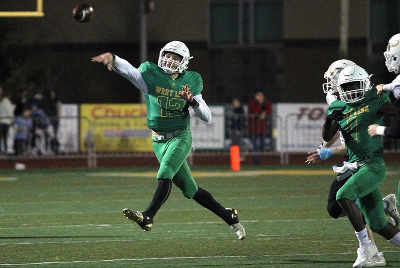 PAMPLIN MEDIA GROUP PHOTO: MILES VANCE - West Linn senior quarterback Ethan Long makes a running throw during his team's 55-20 Friday home win over Lakeridge in the second round of the Class 6A state playoffs.