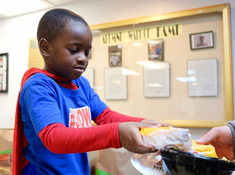 TRIBUNE PHOTO: ZANE SPARLING - Austin Perine, 4, hands out free Burger King burgers to formerly homeless adults at the Men's Residential Center in Portland on Saturday, Nov. 10.