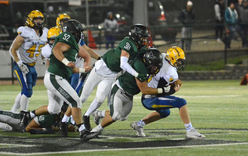 OUTLOOK PHOTO: DAVID BALL - Tigard's Isaia Porter and Andrew Carter bring Barlow QB Jaren Hunter down for one of eight sacks on the night.