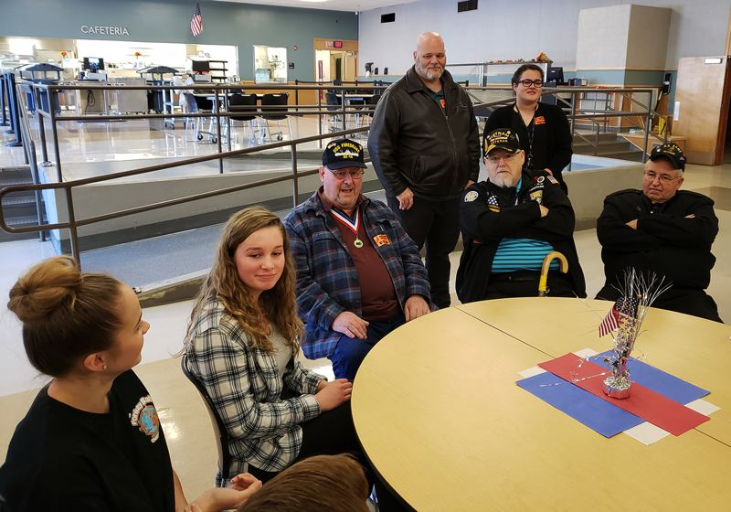 PHOTO COURTESY: LESLIE ROBINETTE - Gladstone High School student leaders Hailey Olson (from left) and Hailey Specht chat with veterans Charles A. Lettenmaier, his son, Charles, and granddaughter Brianna (standing), Gary McAdams (striped shirt) and Jerry Craig at an event honoring former service members on Nov. 8.
