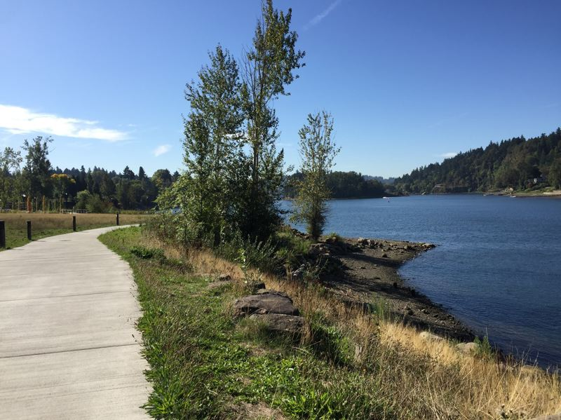 PHOTO COURTESY: NCPRD - A grassy field on the left side of this concrete path at Milwaukie Bay Park is proposed for a playground.